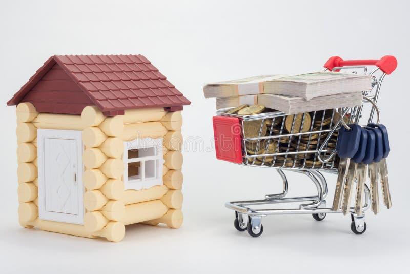 Maison de jouet, chariot avec l'argent et un groupe de clés à la maison photographie stock libre de droits