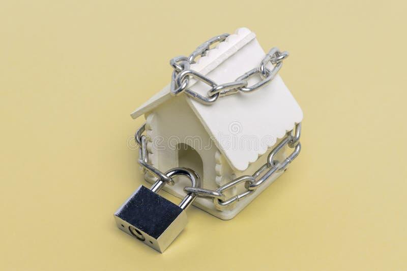 Maison de jouet enveloppée avec une chaîne avec une grande serrure sur un fond jaune comme symbole de l'assurance garantie photos stock
