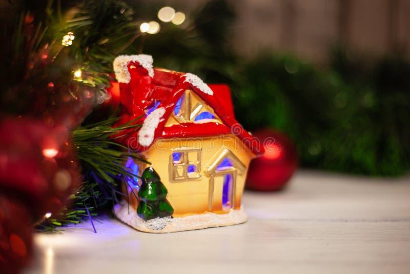 Maison de jouet de Noël avec un toit rouge et des fenêtres avec la lumière bleue photographie stock