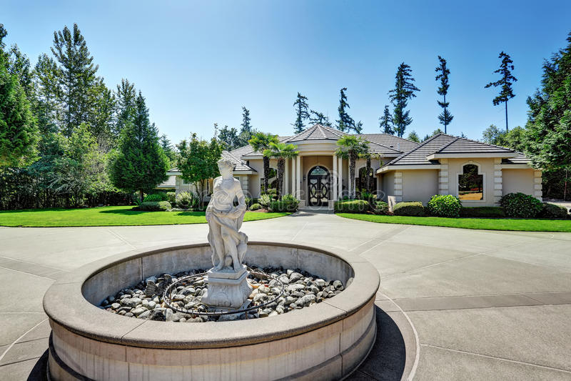 Maison de luxe suburbaine avec la statue de fontaine dans la cour photos libres de droits