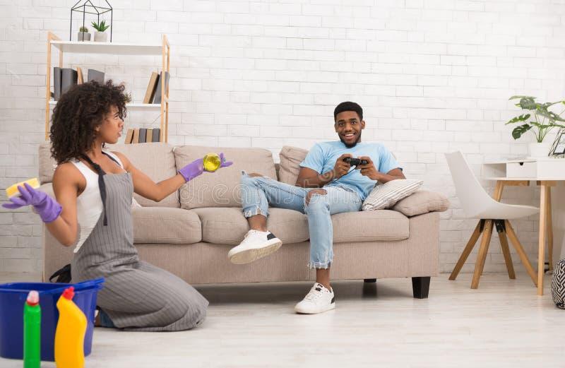 Maison de nettoyage de femme tandis que son ami se reposant sur le divan photos libres de droits