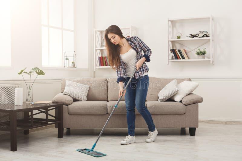 Maison de nettoyage de jeune femme avec le balai photo stock