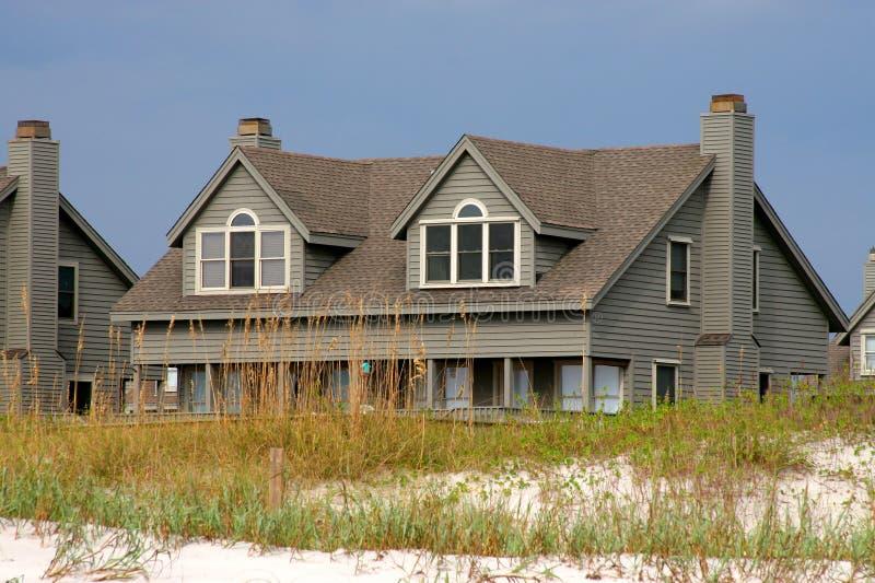 Maison de plage derrière une dune de sable photos libres de droits