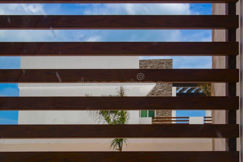 Maison de plage tropicale moderne contre le ciel bleu vu par les lamelles en bois photo libre de droits