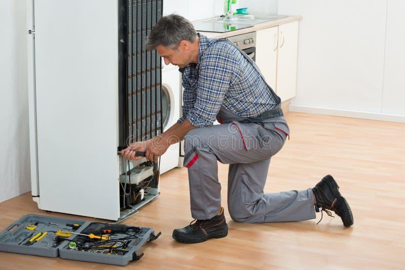 Maison de Repairing Refrigerator At de bricoleur photographie stock libre de droits