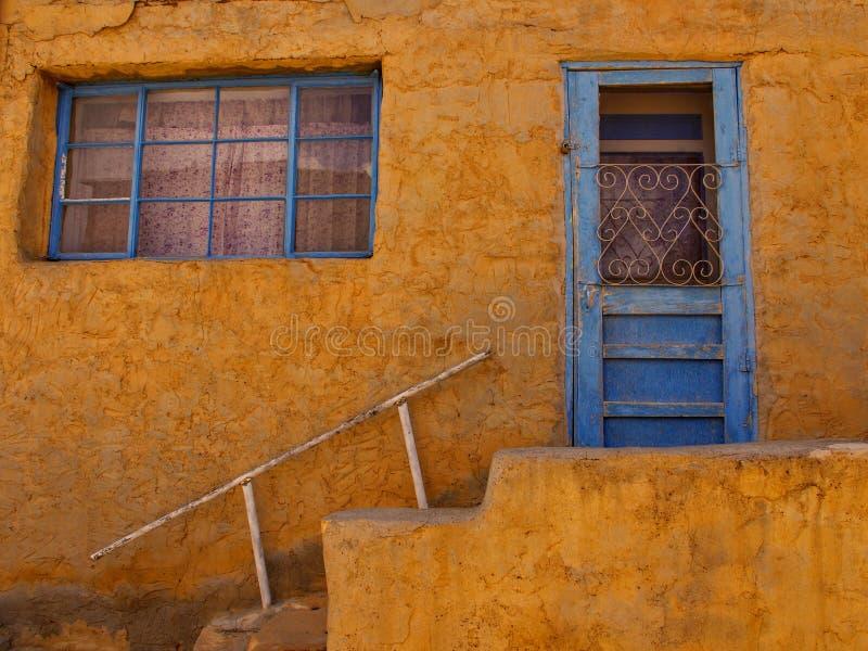 maison de style du pueblo d'adobe au Nouveau Mexique avec la porte bleue images stock