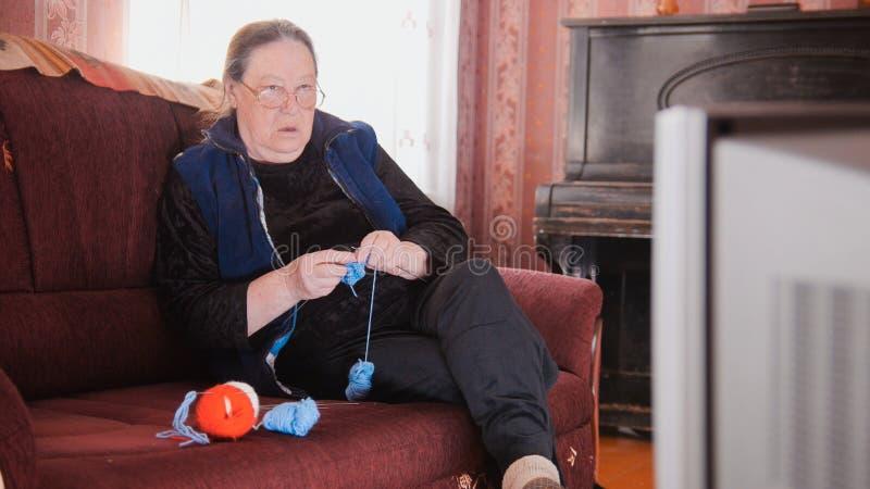 Maison de vieille dame au sofa - chaussettes de observation de télévision de femme supérieure et de laine de knits photos stock