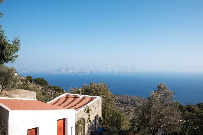 Maison de village de Nisyros avec la mer et les arbres photos stock