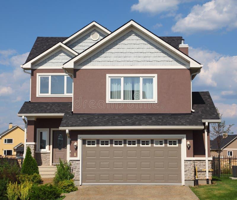 Maison deux-racontée neuve de brique avec le garage image libre de droits