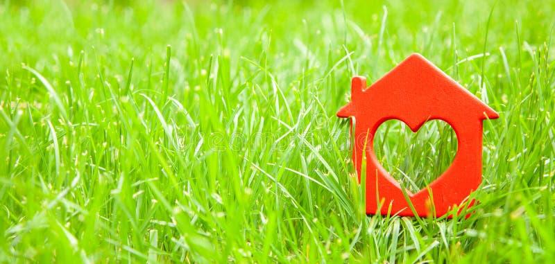 Maison douce dans l'herbe Concept de maison d'eco, cottage Symbole de maison avec le coeur sur la pelouse verte Copiez l'espace p photographie stock