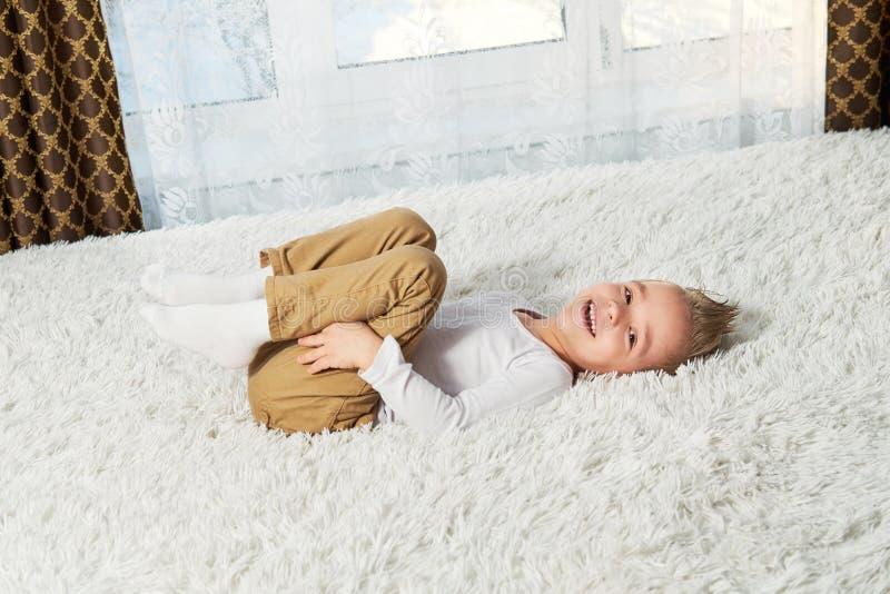Maison drôle d'enfant Mensonge blond de garçon heureux sur le lit mou de couvre-lit, vue supérieure Petit enfant riant tout en re image stock