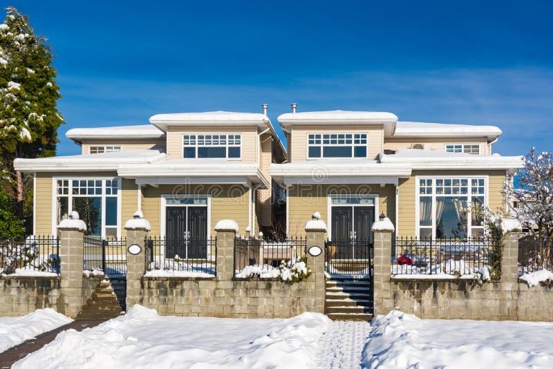 Maison duplex résidentielle avec la cour dans la neige le jour ensoleillé d'hiver au Canada photos libres de droits