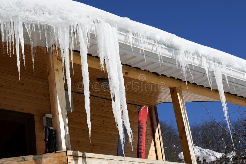 Maison en bois avec la corniche de neige et glaçons sur l'équipement de toit et de ski photos libres de droits
