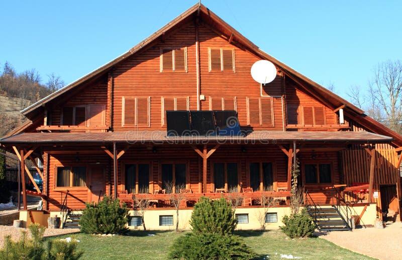 Maison en bois avec les panneaux solaires image libre de droits