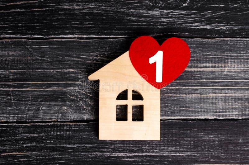 Maison en bois avec un coeur rouge sur un fond des conseils en bois noirs Une icône d'avis pour l'application Nid d'amour, amour photo libre de droits