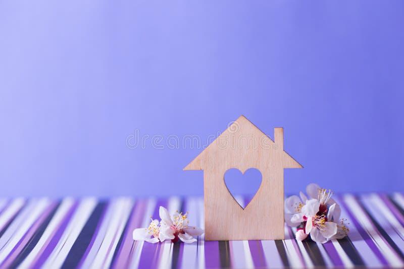 Maison en bois de plan rapproch? avec le trou sous la forme de coeur entour?e par les branches d'arbre fleurissant blanches sur l photos stock