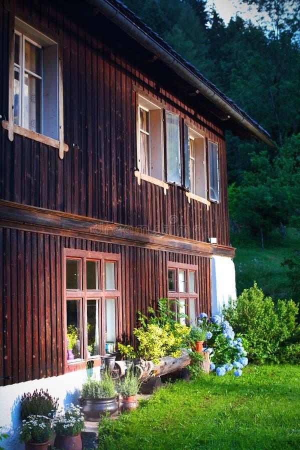 Maison en bois de village avec la fleur, allumée par lever de soleil image libre de droits