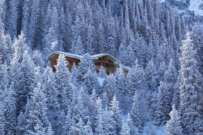 Maison en bois en forêt de montagne de l'hiver photos libres de droits