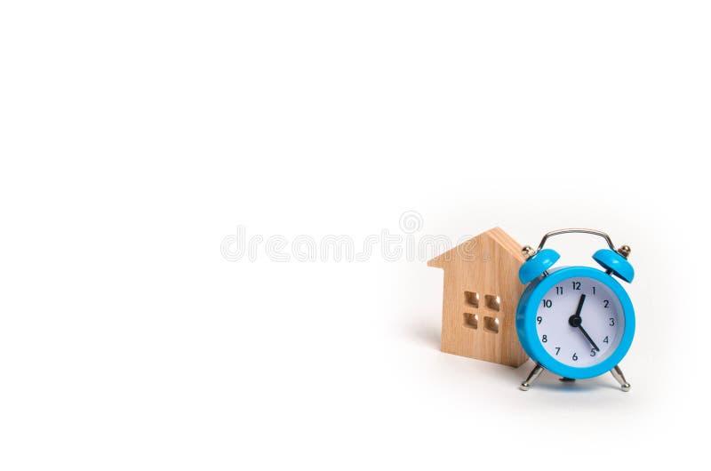 Maison en bois et réveil bleu sur un fond blanc Le concept du loyer logeant la revue mensuelle et d'heure en heure Acco abordable photographie stock libre de droits