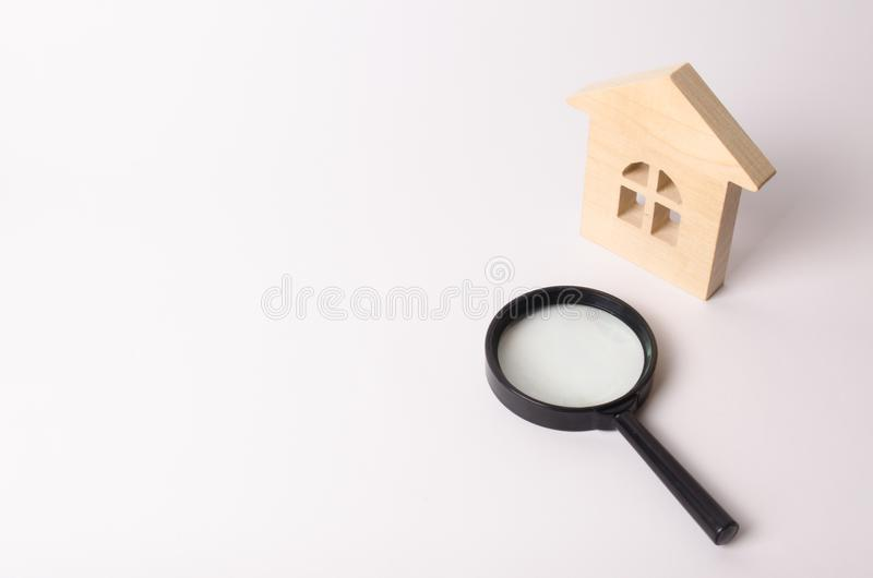 Maison en bois et une loupe sur un fond blanc Le concept de trouver une maison, d'acheter ou de louer un appartement realtor photos stock