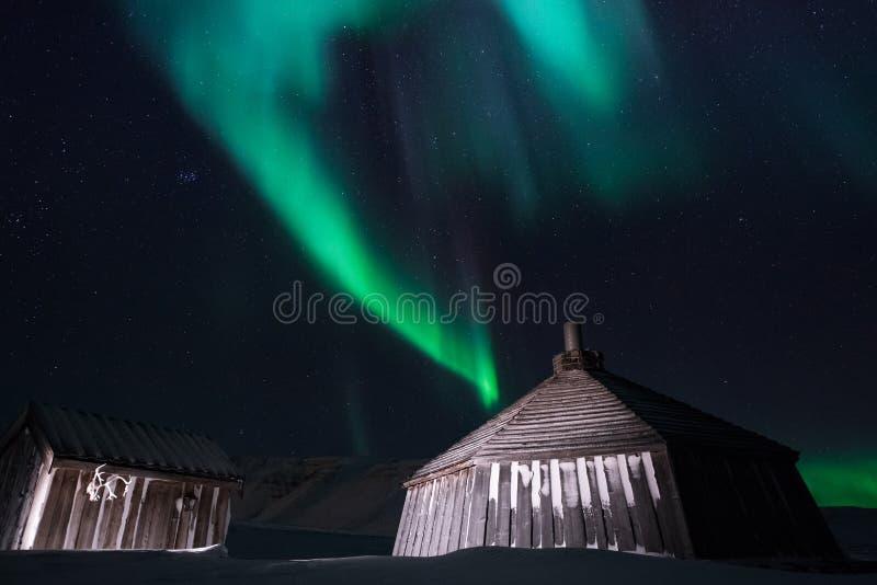 Maison en bois, hutte de yurt sur le fond que l'aurora borealis du nord polaire s'allume photographie stock libre de droits