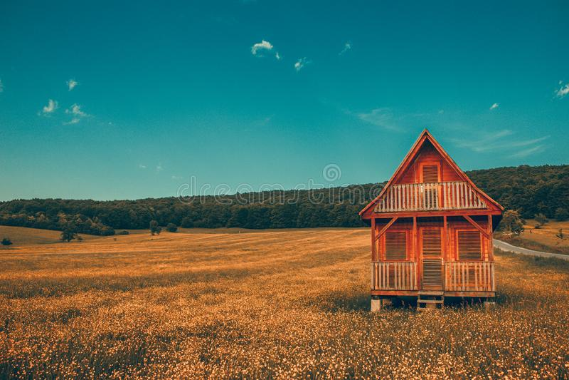 Maison en bois isolée de paysage fantastique dans les montagnes/collines avec la forêt en colline de pré de fond avec des gradi j images libres de droits