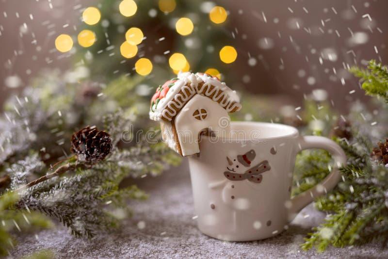 Maison en pain d'épices miniature sur une tasse Effet neige photo stock