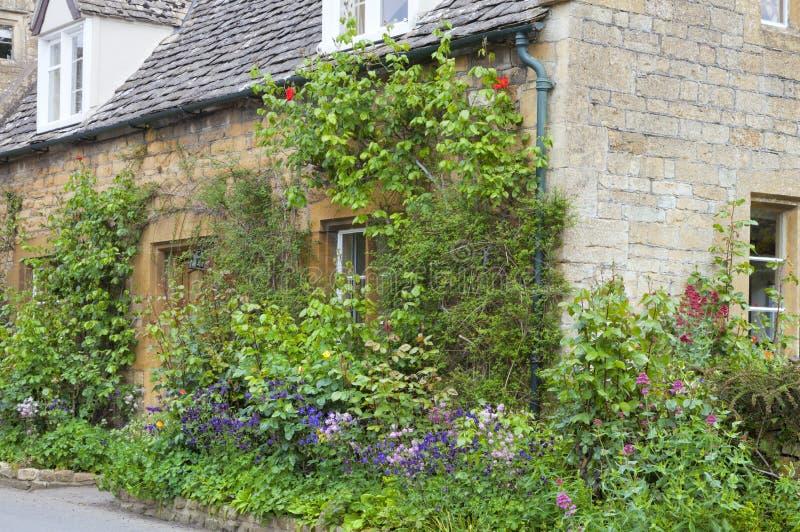 Maison en pierre anglaise avec le jardin coloré d'avant de cottage photos libres de droits