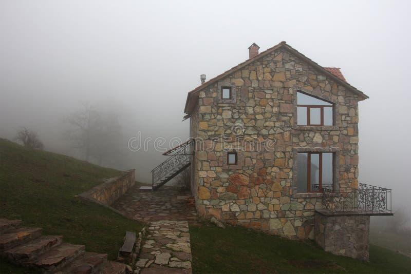 Maison en pierre isolée sur la colline en brouillard, vue de côté photos libres de droits