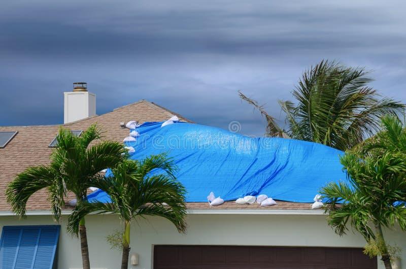 Maison endommagée par tempête avec la bâche protectrice images stock