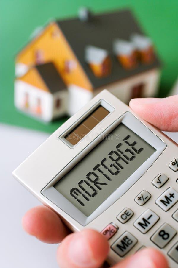 Maison et main de famille tenant une calculette avec l'hypothèque photo stock