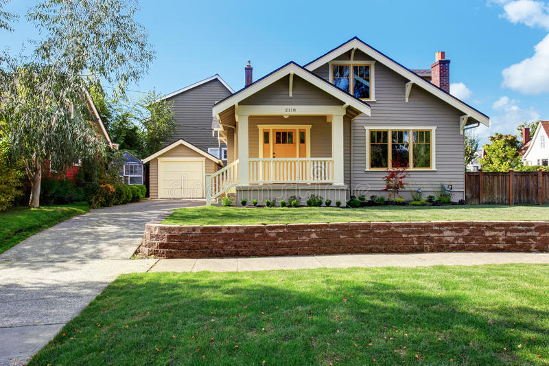 Maison grise extérieure avec le porche blanc et la porte orange images libres de droits