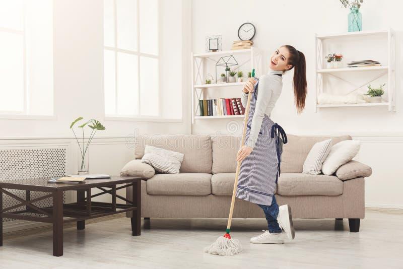 Maison heureuse de nettoyage de femme avec le balai et l'amusement de avoir photos libres de droits