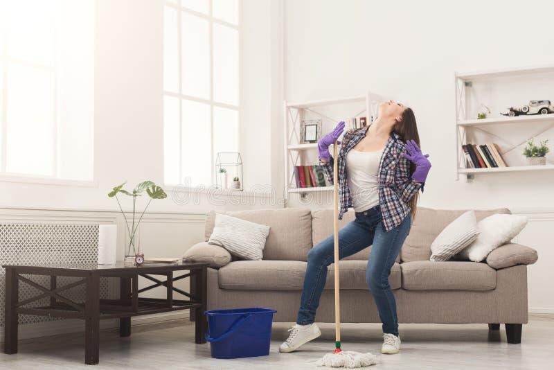 Maison heureuse de nettoyage de femme avec le balai et l'amusement de avoir image libre de droits