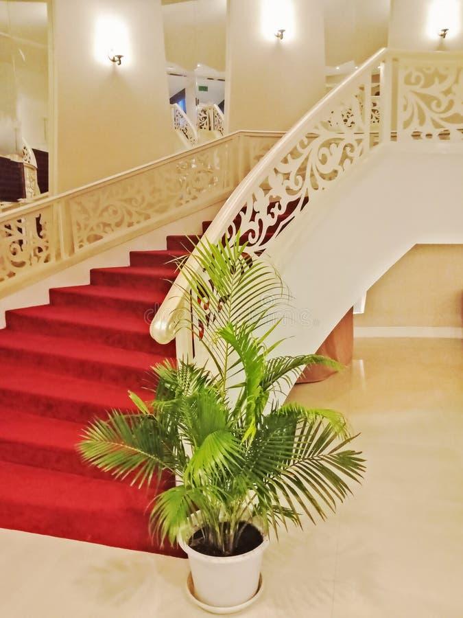 Maison intérieure avec l'escalier et le tapis rouge incurvés photo stock