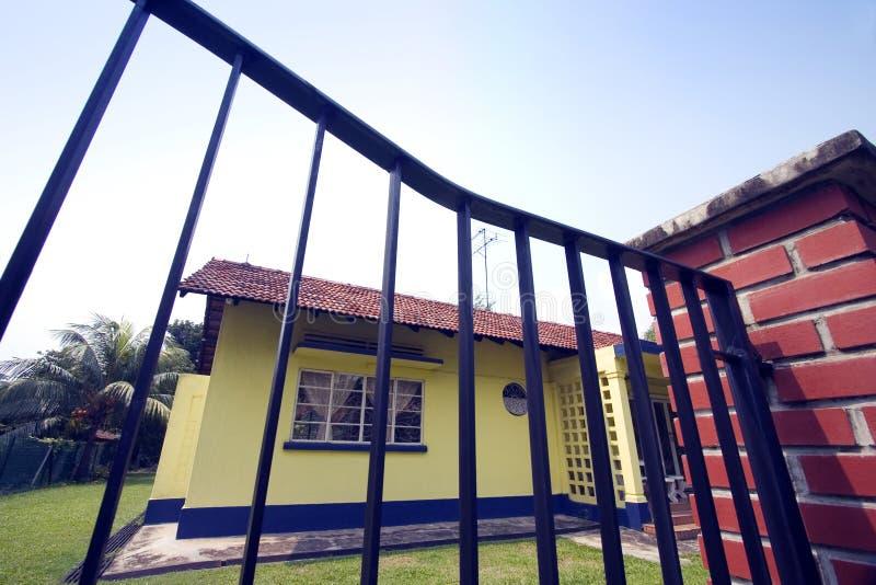 Maison jaune derrière la porte de fer travaillé photo stock