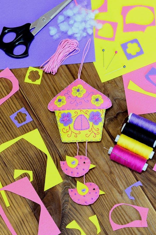 Maison lumineuse faite main avec des fleurs et des oiseaux faits de feutre Belle décoration de mur, matériaux de couture et outil photographie stock libre de droits