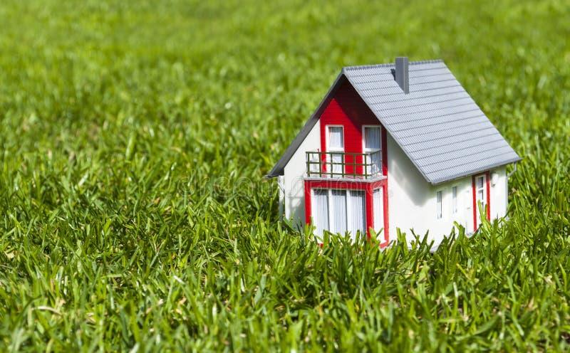 Maison miniature dans le jardin sur l'herbe verte photographie stock