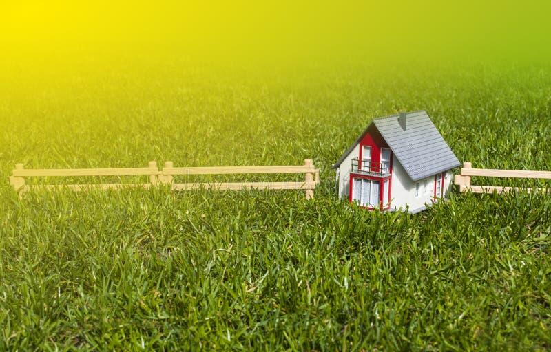 Maison miniature dans le jardin sur l'herbe verte images stock