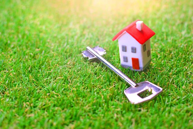 Maison miniature de jouet avec la clé sur une pelouse verte Concept d'une propre maison ou propriété photos stock