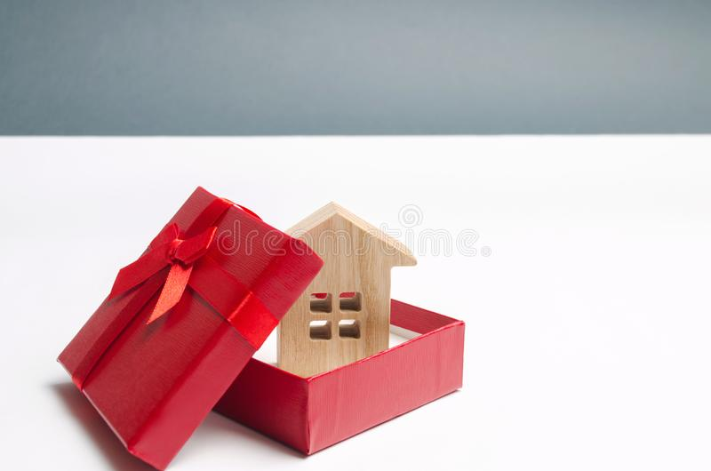 Maison miniature en bois dans un boîte-cadeau Logement comme cadeau Gagnez un appartement dans la loterie Pour hériter de la prop images libres de droits