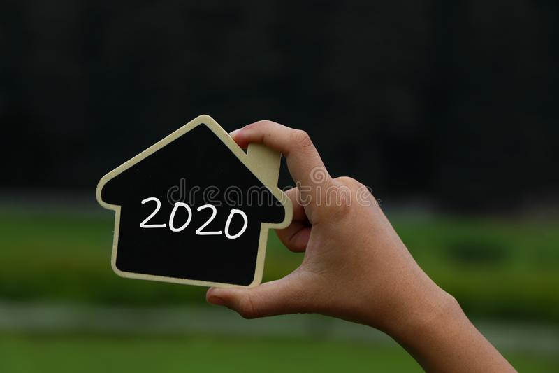 Maison miniature en main avec le texte 2020 dessus image stock
