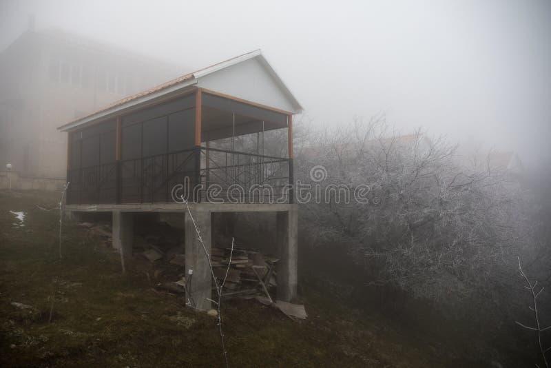 Maison mystérieuse dans la forêt avec le brouillard et un arbre La vieille maison fantasmagorique sur la terre de nulle part image libre de droits
