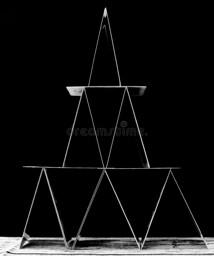 Maison noire et blanche de trois étages de carte dans l'équilibre sur un fond noir photographie stock libre de droits