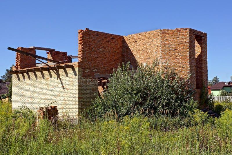Maison non finie de brun de brique envahie avec l'herbe verte et la végétation images libres de droits