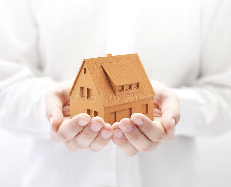 Maison orange dans des mains image stock