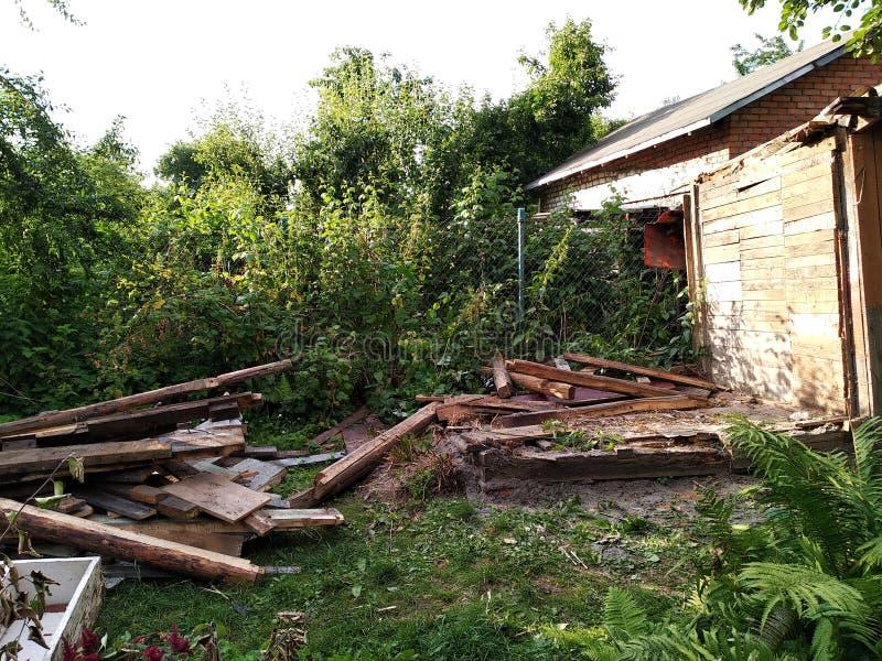 Maison ou annexe ruinée après l'ouragan démonté sur les panneaux du vieux bâtiment, les déchets autour de la maison photos libres de droits
