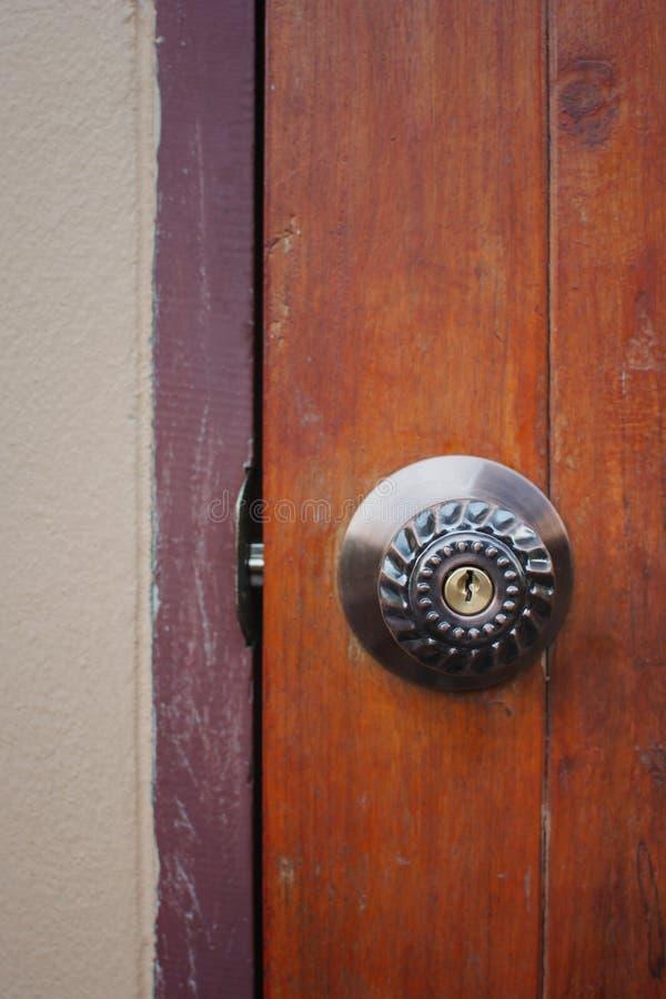 Maison ouverte molle de bouton de porte en métal de foyer sur une vieille porte en bois, sele photo stock