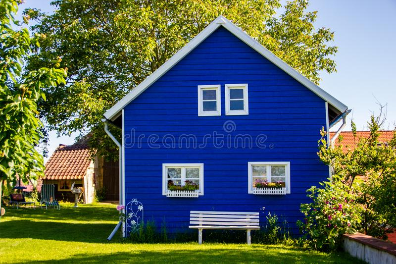 Maison peinte bleue non identifiée de jardin dans le style de construction scandinave photos stock
