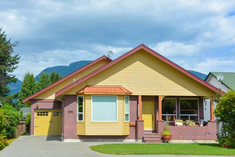 Maison résidentielle jaune avec la pelouse précise et allée concrète au garage images stock